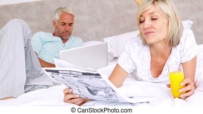 Couple relaxing on bed in the morning at home in bedroom