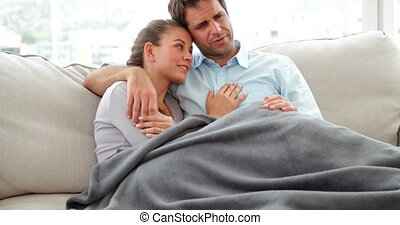 Cute couple lying on couch chatting under a blanket at home...