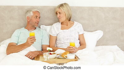 Couple enjoying breakfast in bed together at home in bedroom