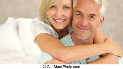 Couple embracing and smiling at camera in bed together at...