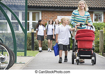 A woman with a pushchair walking her son home from school