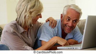 Cheerful couple using laptop together at home in the living...