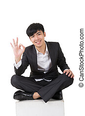 Asian businessman sit and give you an okay sign, full length...