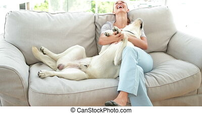 Laughing woman petting her labrador dog on the couch at home...