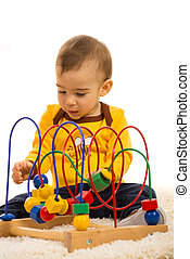 Toddler boy playing with wooden toy and sitting on fur...