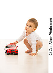 Toddler boy playing with red car - Toddler boy playing with...
