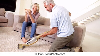 Man hoovering the carpet while partner relaxes at home in...