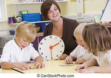Teacher helping schoolchildren learn to tell time in primary...