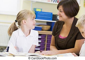 A schoolgirl and her teacher reading in a primary class