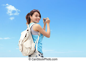 Happy woman traveler photo by camera with blue sky