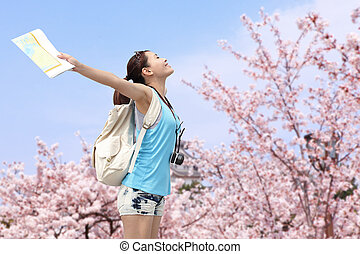 Happy woman traveler relax feel free with cherry blossoms...