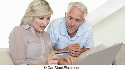 Couple shopping online on the couch at home in the living...