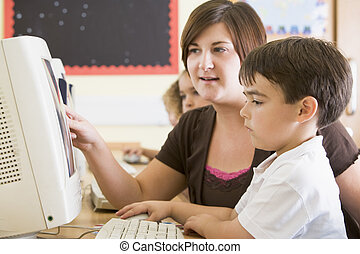 A boy and his teacher working on a computer at primary...