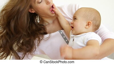 Pretty young mother playing with baby girl on the bed at...