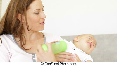 Pretty young mother feeding her baby girl her bottle at home...