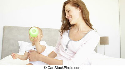 Smiling young mother feeding her baby girl her bottle at...