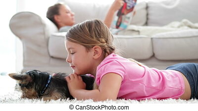 Little girl playing with puppy with her mother reading on...