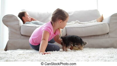 Little girl playing with puppy and bone with her mother...