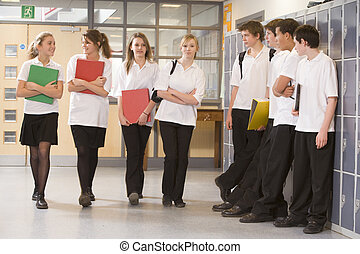 Teenage boys watching girls walk down a school corridor