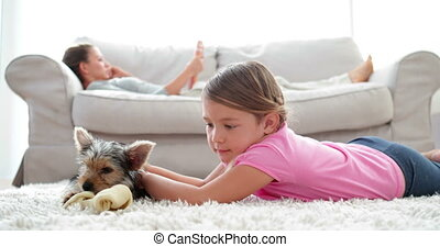 Little girl playing with puppy chewing bone with her mother...
