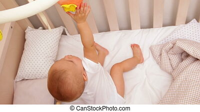 Cute baby girl standing up in her cot playing with mobile at...