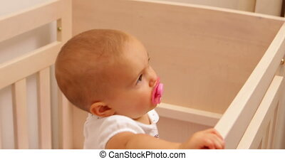 Cute baby girl standing in her cot at home in bedroom