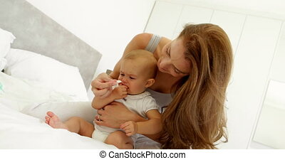 Mother hugging her baby daughter and smiling at camera at...