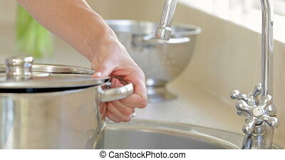 Woman straining pot of water into the sink at home in the...
