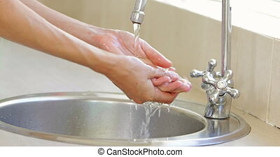 Woman washing her hands at the sink at home in the kitchen