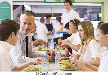 A teacher eating lunch with his students in the school...