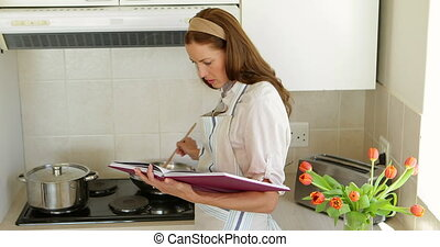 Pretty woman reading a recipe while making dinner at home in...