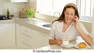 Pretty woman talking on the phone at breakfast at home in...