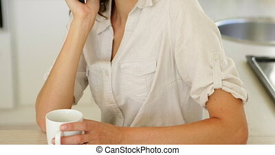 Pretty woman drinking coffee and chatting on phone at home...