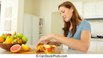 Pretty woman preparing a fruit salad smiling at camera at...