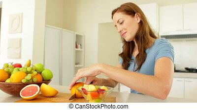Pretty woman preparing a fruit sala
