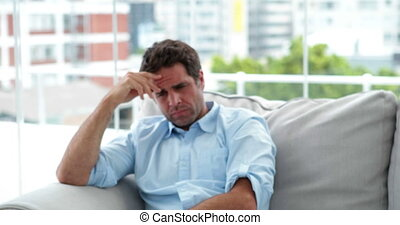 Stressed man sitting on the sofa at home in the living room