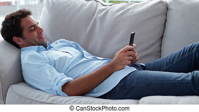 Casual man lying on the sofa sending a text message at home...