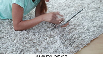 Pretty woman lying on floor using her tablet pc at home in...