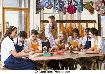 Schoolchildren and teacher sitting around a table in art...