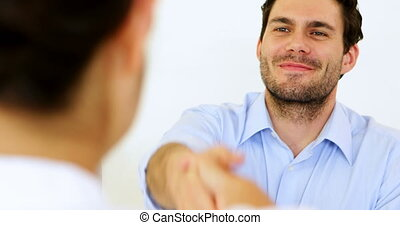 Businessman shaking hands with job applicant in the office