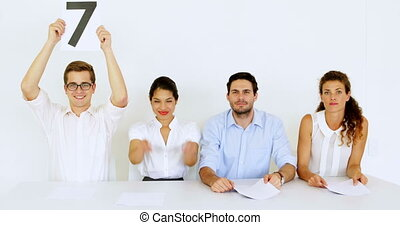 Interview panel holding up high scores in the office