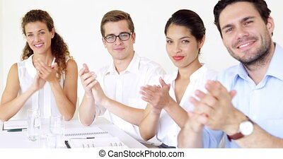 Business people applauding the camera in the office
