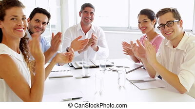 Team of business people clapping at the camera in the office
