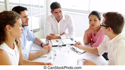 Business people listening to colleague during meeting in the...