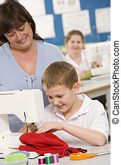 Teacher and schoolboy using a sewing machine in sewing class