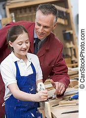 Schoolgirl and teacher in woodwork class