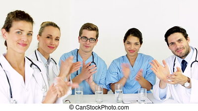 Medical team applauding at the camera in the board room at...