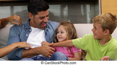 Family tickling each other on the couch at home in the...
