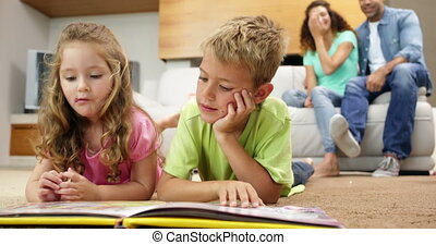 Siblings lying on floor read book with parents behind them...