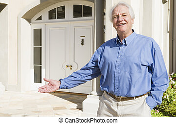 Senior man standing outside house - Senior man welcoming...